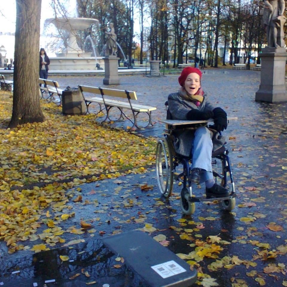 Agnieszka Bal (foto 2017) na starym wózku, z nieodłączną tablicą literową, dzięki której porozumiewa się z nami.